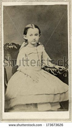 CIRCA 1863 A vintage Cartes de visite photo of a young girl sitting in a chair and wearing a dress with pig tails in her hair. A photo from the Civil War Victorian era. A digital copy of this photo can be purchased at the above web link.