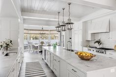 Vintage polished nickel lanterns hang from a white shiplap ceiling above a white island fitted with white shaker cabinets and a honed white marble countertop finished with a curved stainless steel sink with a polished nickel gooseneck faucet. Kitchen Designs Photos, White Shaker Cabinets, Cottage Kitchens, White Kitchens, Beach Kitchens, South Shore Decorating, White Shiplap, Living Room Shop, White Houses