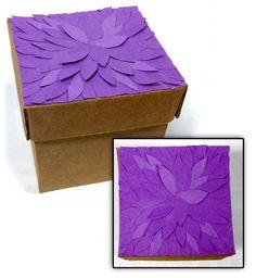 Caja de cartón con detalle de flor en la tapa. Hecha de materiales reciclados.