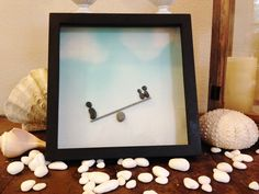 """Pebble Art """"Seesaw """" Beach Decor Stone Rock People Baby Shower Gift. Seesaw Pebble art of beach stones and driftwood gathered form the Pacific Coast of Washington State. 11 X 11 X 1 3/4 inches outside dimensions Flat Black Shadow box frame . Ships same or next day VIA USPS Priority Mail 1 to 3 days delivery in the USA."""