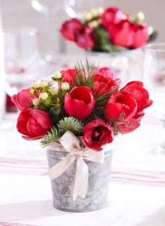 Arrange red tulips alongside pine branches and snowberries for maximum contrast. More Christmas centerpieces: http://www.midwestliving.com/homes/seasonal-decorating/easy-christmas-centerpiece-ideas/page/36/0