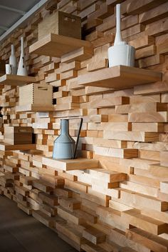 Unique stacked wall of uneven pieces of wood, with the longer ones used as shelving for decorative objects.