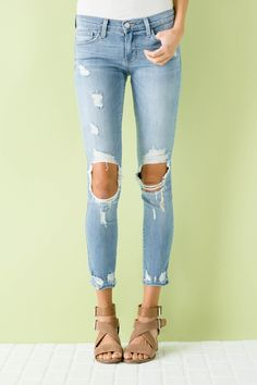 Our Long Weekend Flying Monkey Cropped Skinnies feature a standard 5 pocket style, front button enclosure, and a light blue wash denim, knee, hem and front panel distressing, and gold stitching. - Unl