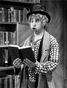"""""""Harpo Marx, enjoying a good read with his usual critical acuity. Marx, who was named Adolph at birth and changed his legal name to the less Germanic Arthur in 1911, was a great favorite of many writers who were his contemporaries. He was close friends with Robert Benchley, Alexander Woollcott, George S. Kauffman and S. J. Perelman, among others."""""""