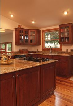 Log cabin style with modern comforts? Yes please!  Cabinets and island are cherry wood and the countertops are medium tone granite.  Rustic Kitchen by Kitchen Saver
