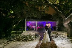 Winter wedding. Bride and groom brave the cold Texas winter. Black fur. Bliss Bridal gown. Black tux. Night photo. Purple Lights. Ice Storm. Texas Wedding. Fort Worth Wedding. Classy. Elegant. Wedding reception at Stonegate Mansion of Fort Worth. Photo by Amanda with Lightly Photography.
