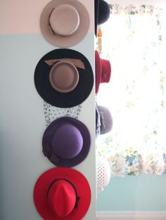 granted, my studio isn't the stuff of dreams, but i store my purses on a wall in my walk-in closet, kinda like these hats. a little whimsy for a boring space, and it encourages me to keep everybody in rotation :)