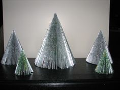 Christmas trees made out of magazines. These ones SPARKLE!! I wonder if my kids could make these?