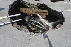 Pamela Knox waits for rescue after a massive sinkhole opened up underneath her car in Toledo, Ohio in this July 3, 2013 photo. Toledo firefighters later rescued Knox without major injuries. Fire officials told a local TV station that a water main break caused the large hole.