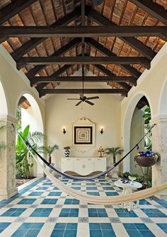 Porch hammocks, graphic blue patterned tile floors and steep wood ceilings with exposed beams in Merida, Mexico.