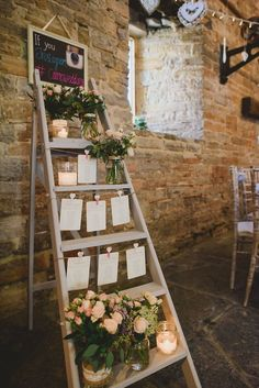 Step ladder table plan with candles, glass jars filled with flowers and strung up stationery - Image by Sam Gibson - Bride wears lace wedding dress at a rustic wedding in Almonry Barn Somerset. Bridesmaids & Groomsmen outfits from Debenhams: