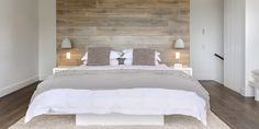 Modern rustic bedroom - this is so serene. Whites, taupes, light ash wood tones. Smooth finish horizontal wood paneled wall as a headboard with modern white side tables. | Capital Building |