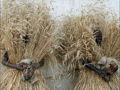 Men dressed in straw outfits hold their devil masks as they wait for the start of the traditional Buttnmandl event in Bischofswiesen, Germany. The pre-Christmas tradition, where costumed people run, shout and ring cowbells, is an ancient pagan ritual for protection against evil spirits.  Matthias Schrader, AP