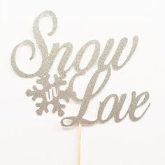Snow In Love Wedding Cake Topper: Confess your love for one another (and maybe for snow, too) once more with this sparkly silver cake topper. Add detailed snowflakes all over the cake for a creative touch. | Creative Winter Wedding Cake Toppers for a Winter Wonderland Wedding