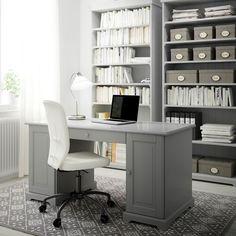 Hemmakontor med grått skrivbord, bokhyllor och arbetsstol med vit bomullsklädsel