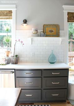 Upper white cabinets, plank walls, island base and trim: Benjamin Moore White Dove Kitchen ceiling: Glidden Polished Limestone Kitchen/pantry/family room walls: Glidden Polished Grey (lightened version of Glidden Wood Smoke) (Family room ceiling: Glidden Wood Smoke) Lower Cabinet Paint: Benjamin Moore Advance Paint (Kendall Charcoal)