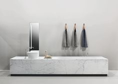 Bathtub Washbasin linear System in Marble Bianco di Carrara with soft fine grain. The classical nature of the Marble blends in with the modernity of the Solid Surface LOOP washbasin, with the stainless steel of the OX taps and of the AIR mirror and with the laquered finish graphite grey of the racks and of the base.
