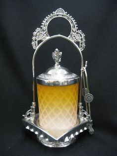 "Victorian Pickle Castor,  diamond quilted mother-of-pearl satin glass insert, apricot to pink, fancy silverplate holder & tongs, signed Rogers, 1883, excellent, 11"". Sold for $250 in 2012"