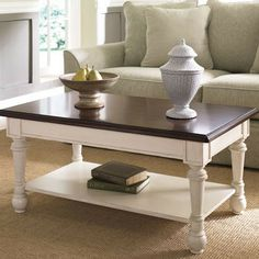 Two-tone table with a bottom display shelf and turned legs. Product: Cocktail table Finish: Distressed fruit...