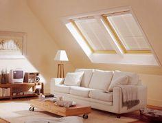 Soggiorno mansardato bianco con mobili in legno.