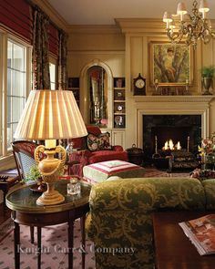 Green and red upholstery done to perfection, creamy wall color, fireplace, Oval side table, awesome crown moulding, art, accessories.....love it all (Knight Carr& Co)