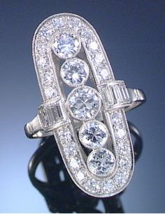 DIAMOND RING, 1930S Designed as an elongated oval open work plaque, collet-set at the centre with five principal circular-cut diamonds, within borders of millegrain-set baguette and circular-cut diamonds.