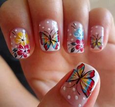 Butterfly nail art designs are the way to go when you want cool looking nails. This design features a white French tip and polka dot design, added with colorful flowers with butterflies on top of them. The butterflies are created with a combination of red, blue, yellow, green and black colors.