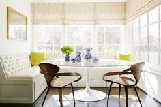 This window lined dining space combines white bench seating with matching wooden armchairs, and a white round table.