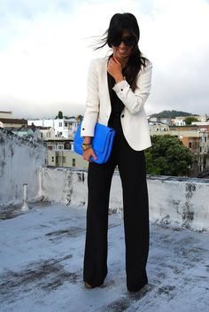 black pants and top. white cream blazer. accent clutch bag.