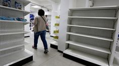 A woman walks past empty shelves at a drugstore in Caracas, Venezuela, February 23, 2016.