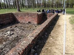 A group sitting at the ruins of gas chamber and crematorium no. 2. The structure here is the changing room where people had to strip before entering the gas chamber.
