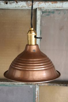Hardware store lamp reflector spray painted gold or copper as hanging light. Industrial / steampunk look