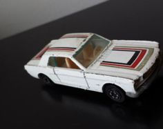 "Vintage Collectible Yat-Ming 66' Mustang Toy Car $22.00 | This is a vintage collectible toy Yat Ming classic 1966 Ford Mustang No. 1073.  It is in good vintage condition with some basic surface wear.  It is white with black, red, and gold stripes and has the opening/closing doors.    The bottom reads: yatming Made in Hong Kong (sticker) 66 Mustang No. 1073  Measurements:  -- 3"" length -- 1 1/4"" width --  7/8"" height"