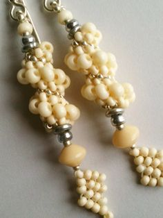 Cream spiral beaded earrings by Jeka Lambert.  Seed bead woven.  Seed beads, glass beads, metal heishi disks.