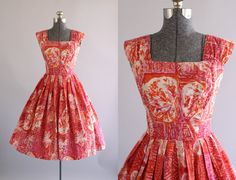 This 1950s Made in Hawaii cotton dress features an amazing atomic hibiscus floral print in shades of red, fuchsia and orange.