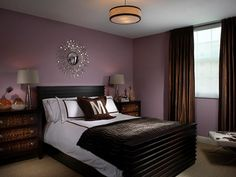The deep lavender walls and chocolate brown draperies keep this bedroom dark to make it easy to relax.