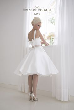 On trend simple mikado 1950's inspired tea length wedding dress with a contemporary twist. Full circle skirt with pockets lead to a fitted stuctured bodice with square neckline. To the rear are delicate bows to offer a girlie touch and a blush pink leather belt. www.houseofmooshki.com/our-dresses/faye