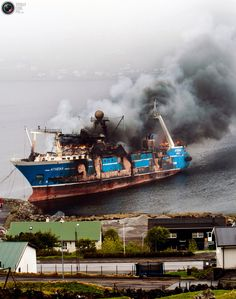 Smoke rises from the ship Athena, one of the largest fishing boats in the Faroe Islands, in the port of Runavik in the Faroe Islands May 9, 2011. The ship was undergoing refurbishment when it caught fire and the cause of the fire is under investigation, according to local authorities. REUTERS/Palma Jacobsen/Stringer