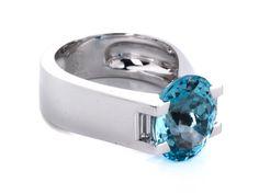 "Ringweite: 52. Gewicht: ca. 19,1 g. WG 750. Signiert ""Cartier I77190"". 1999. Strenger, massiver Ring mit oval facettiertem, hellem Aquamarin, ca. 4,8 ct,..."