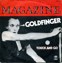 Magazine ‎– Goldfinger / Touch And Go   Tracklist A Goldfinger Written-By – Anthony Newley, John Barry, Leslie Bricusse B Touch And Go Written-By – Howard Devoto, John McGeoch  A is a cover version of the song from the James Bond soundtrack by John Barry