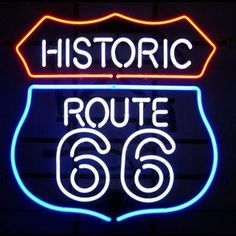 Historic Route 66 Neon Sign featuring multi-colored, hand blown neon tubing. The glass tubes are supported by a black finished metal grid which can be hung against a wall or window. It can even sit on
