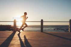 Sportswoman training on seaside promenade at sunset by jacoblund. Side view of fitness woman running on a road by the sea. Sportswoman training on seaside promenade at sunset.