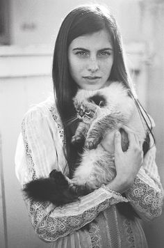 A girl snuggling her Persian cat