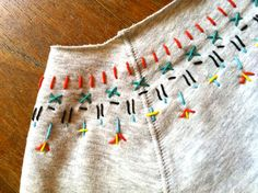 Mit buntem Garn könnt ihr einem einfarbigen Pulli das gewisse Etwas verleihen. Für große und Kleider Kleidungsstücke, eine prima Idee zum selber machen.