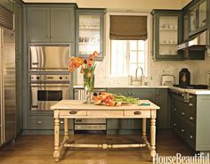 "This California bungalow keeps it simple, and so does its modest kitchen. ""My clients joke that they can burn water, so the kitchen is really set up primarily for entertaining, with that big table as the buffet,"" designer Chad Eisner says. ""We tried a center island, but it looked like a behemoth. Then we found that table. It had been used by an artist and came with lots of scars, which is why no one ever has to worry about staining or cutting it. The built-in millwork and the surrounding ..."