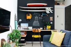 Home office recebeu pintura preta para delimitar a sua área na sala de estar.