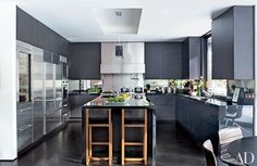 The couple called on Stonefox Architects to renovate and decorate the entire home. Sleek ebonized-oak cabinetry, matching flooring, and black granite counters lend a moody elegance to the revamped kitchen, which is also outfitted with a Wolf range, a Sub-Zero freezer and refrigerators, and BDDW stools | archdigest.com