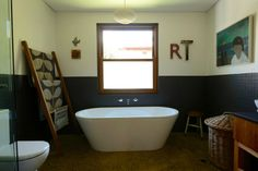 Definitely a bathroom I'd like to spend time in! Lots of modern features including a concrete floor and beautiful soaking tub near a wonderful window for natural light.