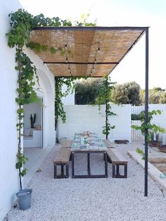 gravel patio with picnic style dining. simple shade for the garden
