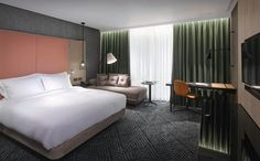 Hilton London Bankside | interior design | hotel design | guestroom | concrete-effect | timber paneling | leather bedhead | black stainless steel | smoked glass